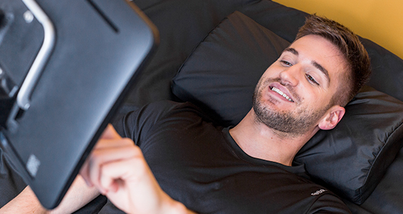 Man lying down in a hydro massage bed looking at a TV